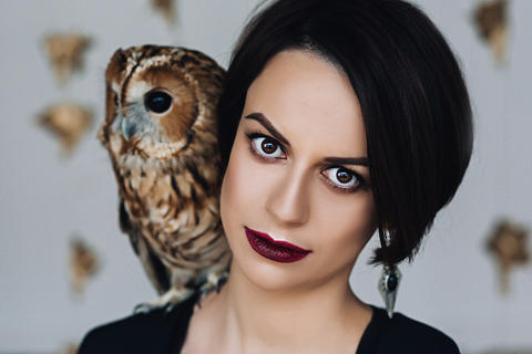 Caucasian attractive woman with make up in black dress with owl on her shoulder Fotografía