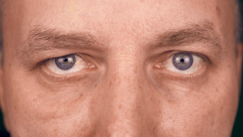 Extreme close up eyes of adult caucasian man. Front view of man face. Man Live Action