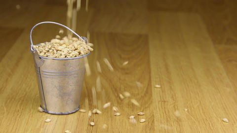 Fall into a bucket of pearl barley grains and on wooden... Stock Video Footage
