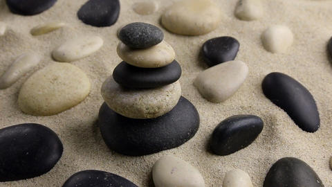 Stones pyramid on sand standing among the rocks, harmony, balance,motion Footage