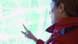 Young woman in red coat using touchscreen outdoors. Female making gestures by Footage