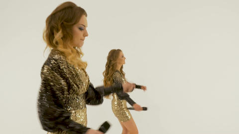 Two beautiful girls sing and dance in the studio, on a white background Footage