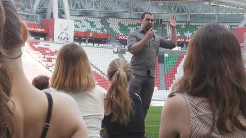 Slow Motion Man Makes Speech in front of Girls Sitting on Field ビデオ