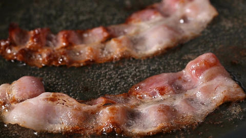 Two bacon slices frying on pan Live Action