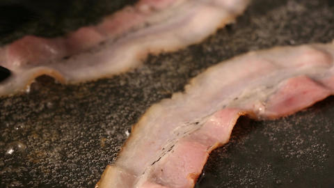 Bacon slices frying on pan Live Action