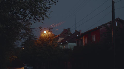 Rain with thunder and lightning in the evening on a street with houses and tall Footage