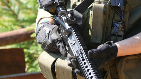 Military standing hand on the trigger of his weapon while standing guard and Live Action