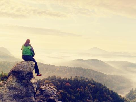 Hiker man take a rest on mountain peak. Man sit on sharp summit and enjoy Photo