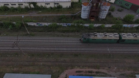 A bird's eye view of a slowly moving cargo train with buildings nearby Footage