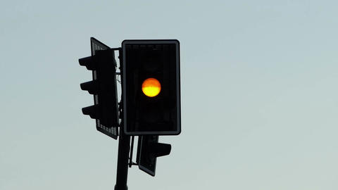 A railroad traffic light shimmering with an orange and ellow light Footage