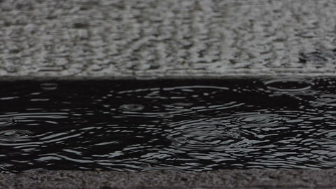 A water pool on an asphalt pavement in a rainy weather in a town Footage