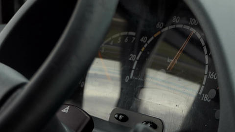 A speedometer on a dashboard of a riding car shows kmph Live Action