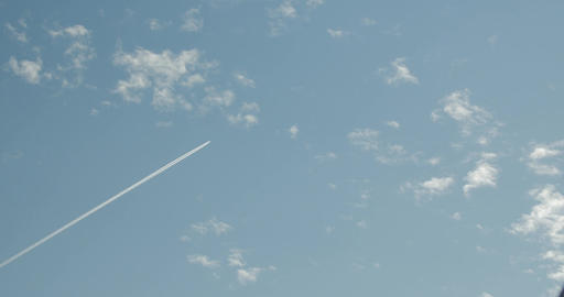A commercial airliner is flying diagonally left to right of the frame in a Footage