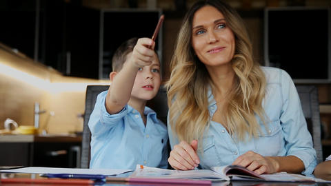 Smiling mother helping his son doing homework, dictates the text to help you Footage