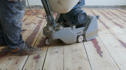 Floor sanding. Sanding machine is removing old surface Footage