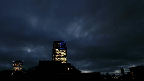 Timelapse of black clouds covering the metropolis at twilight Footage