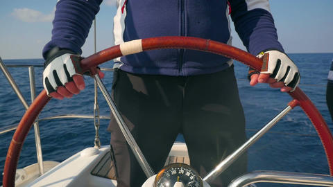 Closeup on skippers hands turning steering wheel at sailing boat Footage