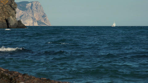 Sea coast with high rocks and a white sailboat in the sea Footage