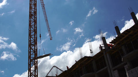 Construction site. Construction crane lifts cargo against the blue sky Footage