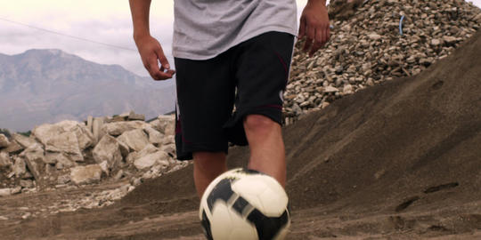 Person juggling soccer ball Live Action