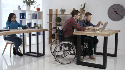Hipster man in wheelchair working in office Footage
