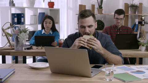 Young businessman having a sandwich at workplace Footage
