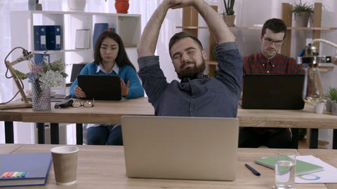 Businessman at the desk stretching arms in office Footage