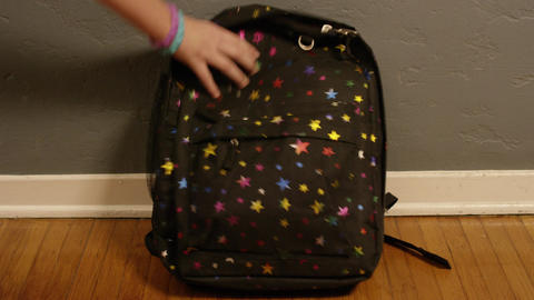 Hand picks up starry backpack, closeup Footage