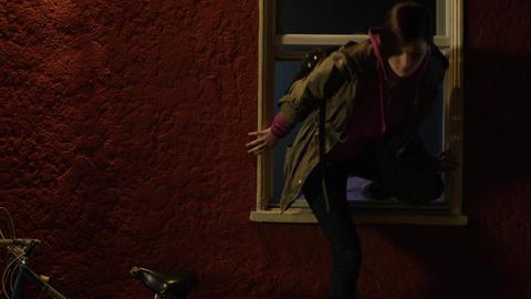 Teenage girl sneaks out of bedroom window Footage