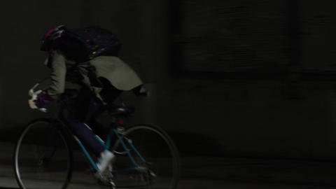 Woman rides bicycle through dark alley Footage