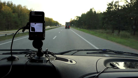 A GPS navigator on a car dashboard shows the route on a highway Footage