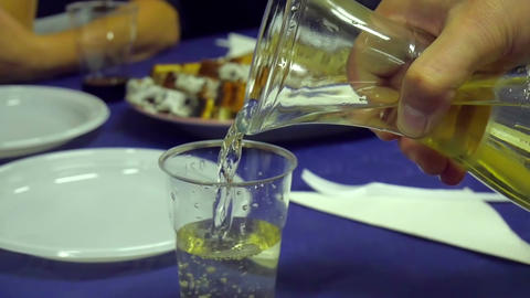 Male hand pouring white wine into plastic glass from glass decanter Footage