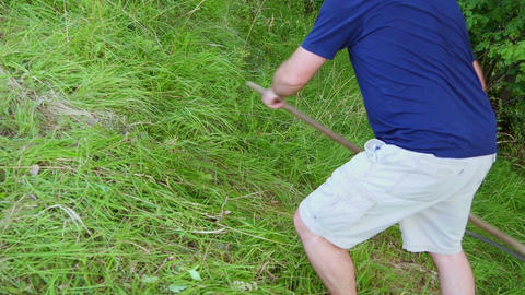 Man mowing grass with a scythe by hands. Mowing on hill slope Footage
