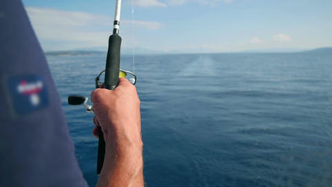 Man holding a fishing rod fishing in sea at back side of sailing boat Footage