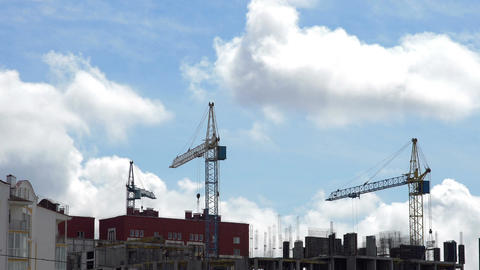 Construction site against a blue sky with floating clouds. Timelapse Footage