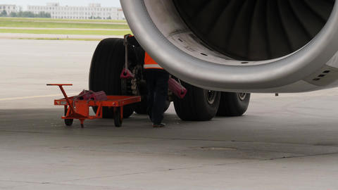 Ground crew member places chocks under aircraft wheels. View from behind jet Live Action