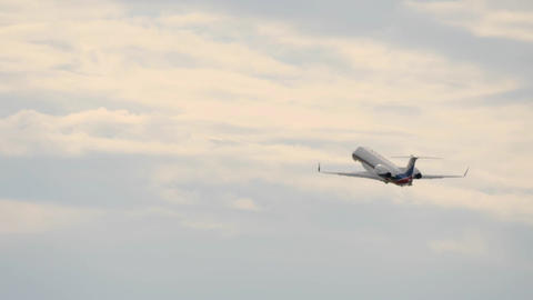 White airplane gains height in overcasted sky after taking off Footage