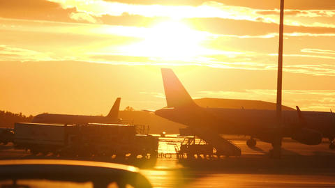 Airplain taxiing at airport ramp and ground support equipment against sunset sky Live Action