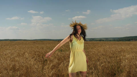 Woman in wheat crown and yellow dress spins round on golden wheatfield at sunny 画像