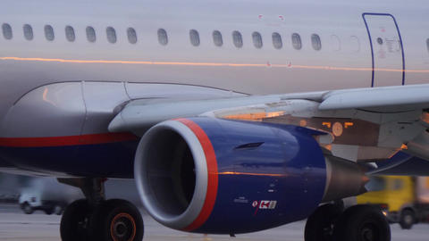 Close up of taxiing jetliner. Sunset light reflects on fuselage Footage