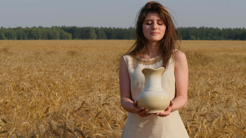 Woman in linen dress holds a jug to the camera standing at gold wheat field Footage