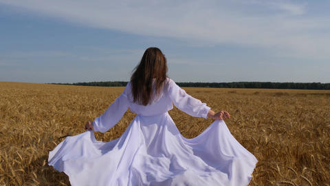 Romantic woman in fluttering white dress walks on goldish wheatfield Footage