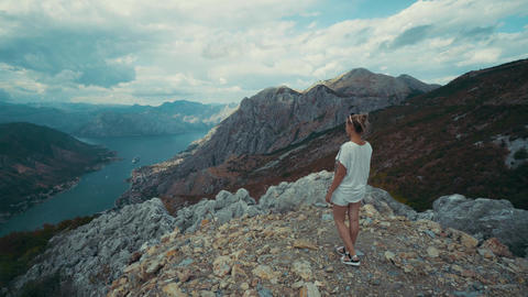 Woman on a stony summit raises arms against sea Bay of Kotor among mountains Footage