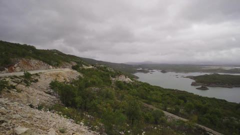 Panning shot of mountain lake with small islend under overcast sky Footage