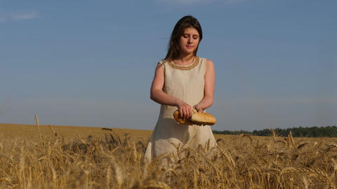 Woman in linen dress stands at cornfield and breakes loaf of bread Footage