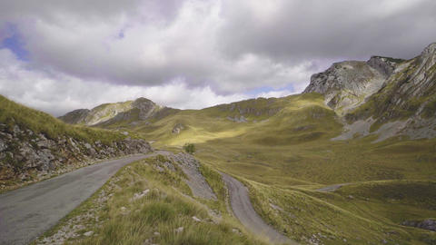 Rocky mountains and grassy hills of Montenegro highland. Sun shines through Footage