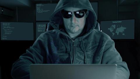 hacker typing at laptop. Man coding on computer dark night. Man in dark glasses Live Action