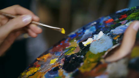 Close up tracking shot of woman's hand mix paints with brush in palette and Footage