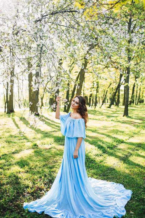 Portrait of beautiful caucasian woman in long dress at the spring blooming フォト
