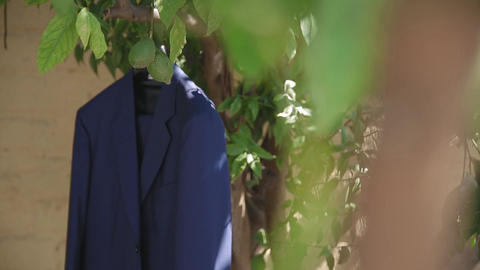 The bride's jacket is hanging in a garden on a tree ビデオ